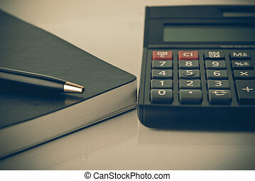 calculator and notebook with pen in finance and banking concept