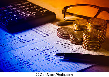 Row of coins,pen,glasses and calculator on the wooden table for finance and banking concept