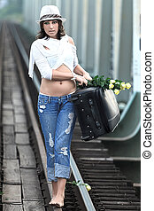 Woman on train track - Young woman on train track holding...
