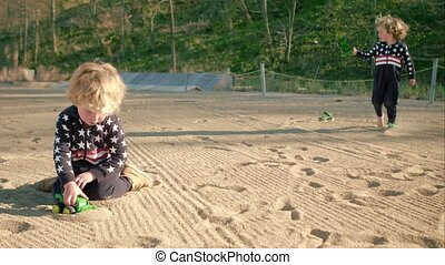 Boys are playing with a toy green dump truck on the beach.
