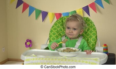 Hungry baby girl with spoon sits at feeding chair and eats...