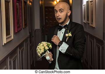 funny elegant bridegroom with a bouquet in hands