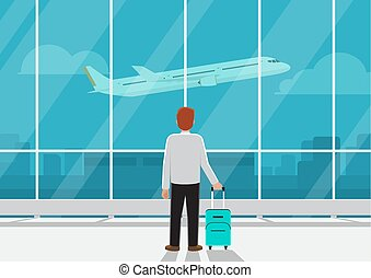 Businessman with luggage in airport looking at airplane in the sky.