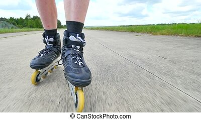 Mans legs roller skating on the asphal. Close up view to...