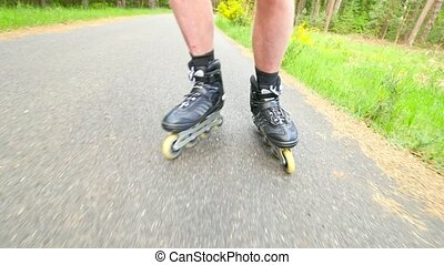 Start inline skating on smooth asphalt in the forest. Close up view to light skin man legs quick movement of black inline boots.