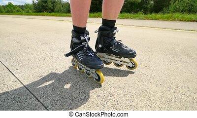 Roller skating and heel braking on the asphalt. Close up...