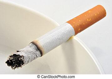 one unhealthy cigarette in a glass ashtray