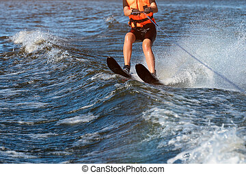 Woman riding water skis closeup. Body parts without a face. Athlete water skiing and having fun. Living a healthy lifestyle and staying active. Water sports theme. Summer by the sea