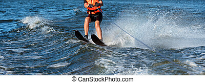 Woman riding water skis closeup. Body parts without a face. Athlete water skiing and having fun. Living a healthy lifestyle and staying active. Water sports theme. Summer by the sea. Banner for website