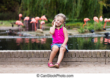 Child watching animals and birds at the zoo