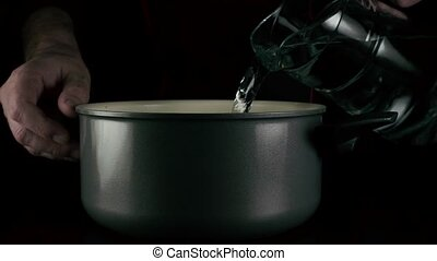 The cook pours the water into the pan. Slow mo - The cook...
