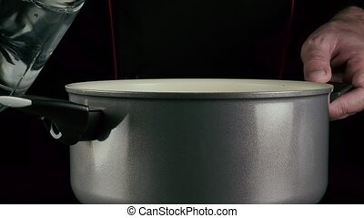 The cook pours water into the pan - Chef pours water from a...