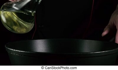 Cook pours oil on a frying pan on a black background