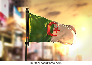 Algeria Flag Against City Blurred Background At Sunrise...