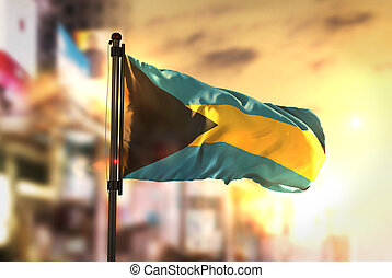 The Bahamas Flag Against City Blurred Background At Sunrise...