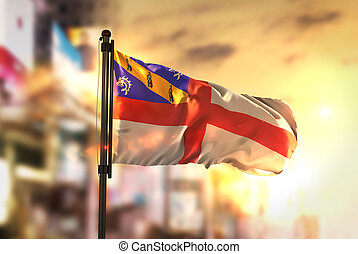Herm Flag Against City Blurred Background At Sunrise...