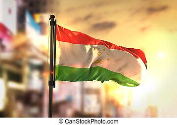 Tajikistan Flag Against City Blurred Background At Sunrise...