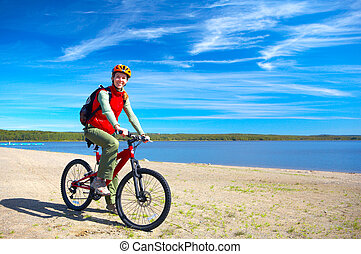 Riding - Young smiling  woman cycling near the lake