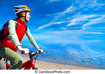 Woman - Young smiling woman cycling near the water
