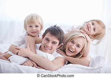 Happiness family - A happy family on white bed in the...