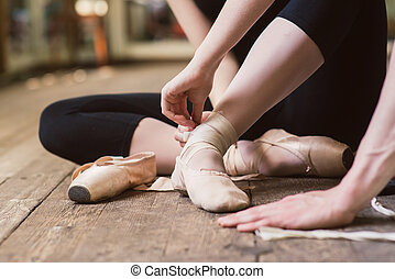 Ballerina putting on her ballet shoes - Young ballerina or...