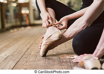 Ballet dancer tying ballet shoes - Young ballerina or dancer...