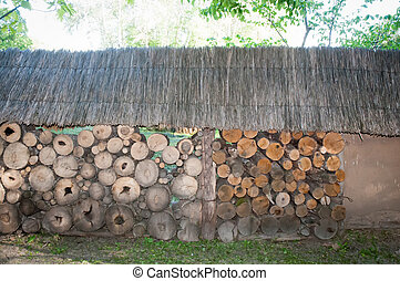 A pile of wooden logs ready for winter, dry chopped firewood stacked in a shed with a straw-covered roof.