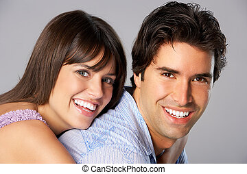 Happy smiling couple in love. Over grey background