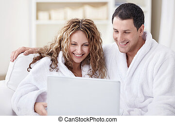 Laughing couple with laptop