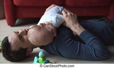 Little child with tender hands on man's shoulder