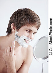 Shaving a man - Young man shaving at the mirror