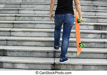skateboarder walking upstairs with a skateboard
