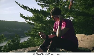Young woman seats on the mountain rocks and listen to music