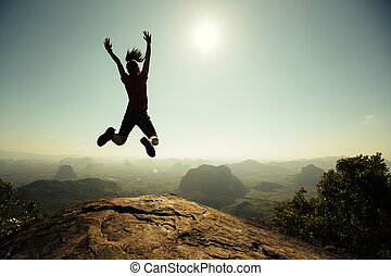 freedom woman hiker jumping on sunrise mountain top