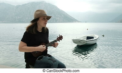 Young woman sits on beach, singing and playing guitar...