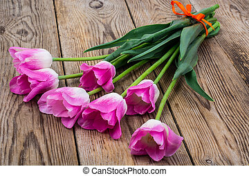 Bouquet of pink tulips on an old wooden table