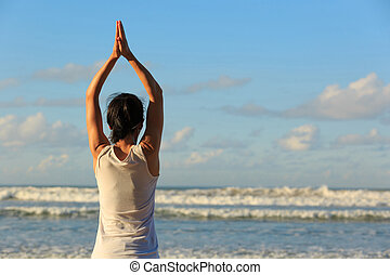 Young fitness woman yoga practice at the sunrise seaside