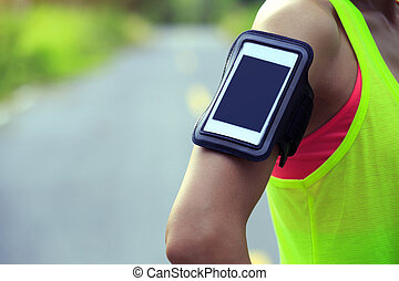 one woman runner wear armband listening music