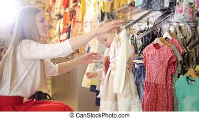 Blonde little girl with mother buying dresses - kids clothes...