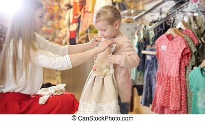 Shopping for kids - cute little girl with mommy buying dress in store of kids clothes