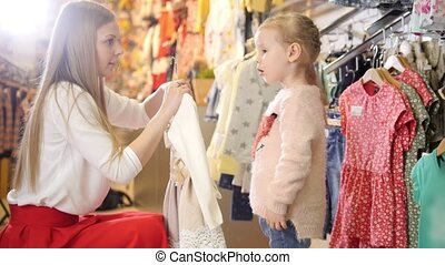 Blonde woman with little daughter buying kids dress in clothes store