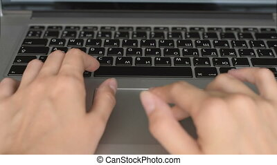 Woman typing on a laptop keyboard - Young woman using...
