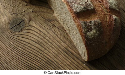 A freshly baked rustic, sourdough loaf of bread on an old...