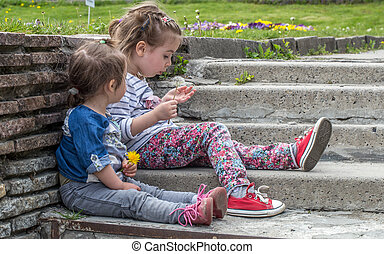 two little girls sitting on the steps outside,the concept of...