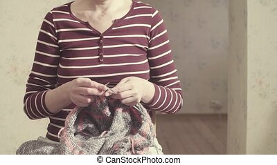 Woman knitting woolen sweater - Woman in the room knitting...