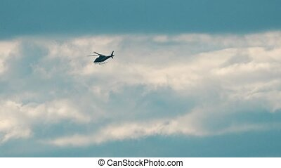 Helicopter flying fast against cloudy sky. 4K telephoto lens...