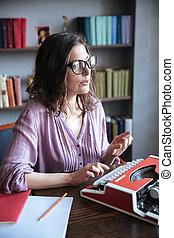 Woman journalist in eyeglasses typing on typewriter indoors...