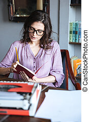 Portrait of a pensive mature authoress in eyeglasses sitting...