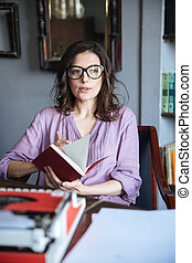 Portrait of a thoughtful mature woman in eyeglasses holding...