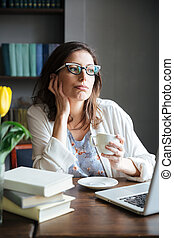 Pensive mature woman holding cup of tea and looking away -...